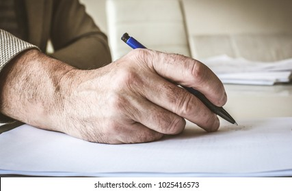 Businessman hand sign papers. Focus on hand. Close up.