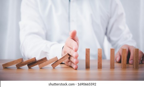 Businessman hand stop falling down of wood block .planing and strategy business disruption concept.