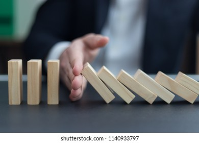 BUSINESSMAN HAND STOPPING DOMINO EFFECT CONCEPT