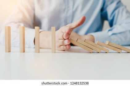 Businessman hand Stopping Falling wooden Dominoes for business solution effect from continuous toppled or risk, strategy and successful intervention. Concept of prosperity in business.