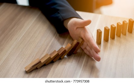 businessman hand Stopping Falling wooden Dominoes effect from continuous toppled or risk, strategy and successful intervention concept for business