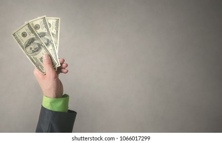 Businessman hand is stretching a dollars money isolated on gray background with copy space background. Financial help. Bribe and corruption. Giving money.