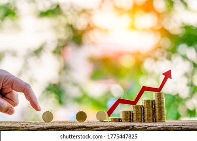 Businessman hand throws a gold coin to saving money and red arrow graph with growing value as destinations in the public park, Loan of decision - making for investment concept.
