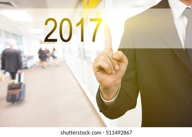 Businessman hand touch 2017 button over blur office background, new year business concept