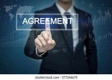 Businessman hand touching AGREEMENT button on virtual screen