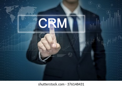Businessman hand touching CRM button on virtual screen