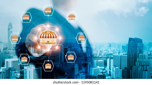 Businessman hand touching icon global network connection on franchise marketing system on city background. Branch of market and customer. Modern technology business. Blue tone.