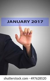 Businessman hand touching JANUARY 2017 message on virtual screen
