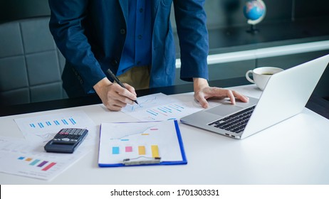 Business-Mann Hand berühren auf aptop und Calculator, Arbeit auf Laptop-Computer mit Business-Dokument auf Schreibtisch. Prüfung des Geschäftsdokuments durch Geschäftsführer im modernen Büro, Nahaufnahme