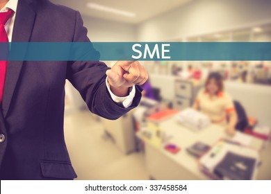 Businessman hand touching SME (Small and Medium Enterprises) sign on virtual screen vintage color