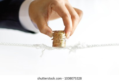 Businessman hand try to sustain balancing and protect a golden coins row on almost absent rope, investment and financial concept