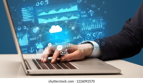 Businessman hand typing on laptop with reports and graphs concept around