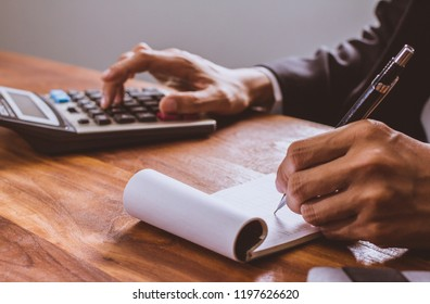 businessman hand using calculator Calculating bonus(Or other compensation) to employees to increase productivity.Writing paper on desk.Selective Focus