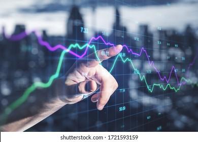Un homme d'affaires utilisant un graphique en chute sur l'interface écran avec l'index. Le concept commercial et financier. Double exposition