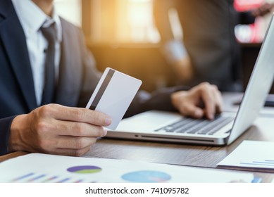 Businessman hand using laptop compter with holding cradit card payments online shopping or business.