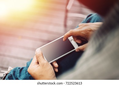 Businessman hand using mobile phone at coffee shop in morning light