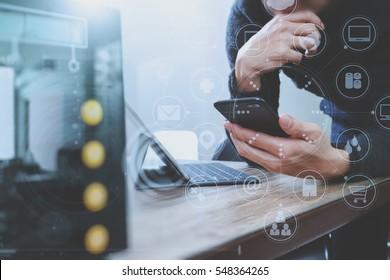 businessman hand using smart phone,mobile payments online shopping,omni channel,digital tablet docking keyboard computer,compact server on wooden desk,virtual interface icons screen