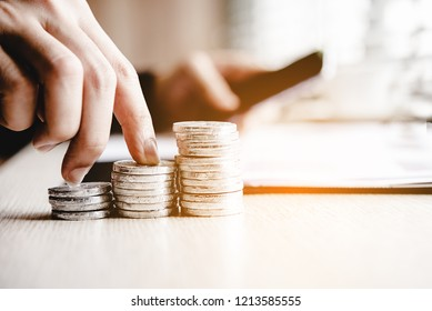 Businessman hand walking stack of coin money for the investment financial report. Investment concept.