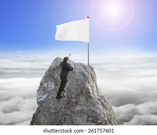 Businessman hand wanting for victory white flag on mountain peak with sunlight cloudscape background