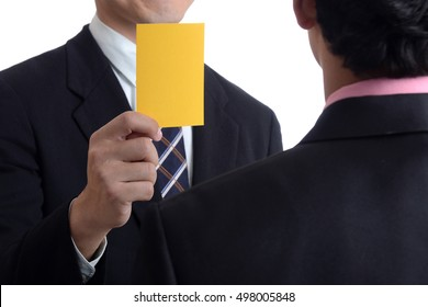 Businessman hand warning with yellow card isolated on white
