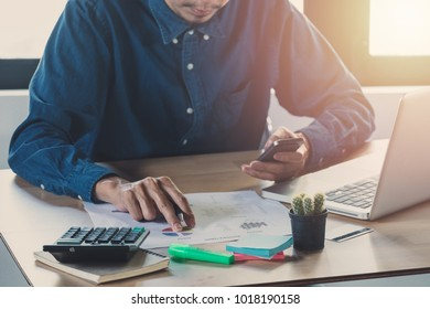 Businessman hand working with business graph or analysis chart and using lsmart phone .Close up business team analysis and strategy concept with sun flare.