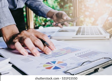Businessman hand working  with business graph or analysis chart and using smart phone .Close up with sun flare.Business analysis and strategy concept.