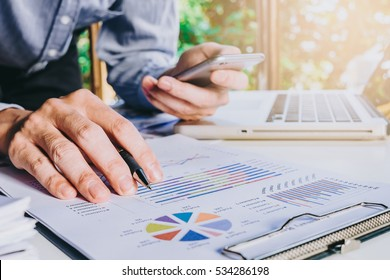 Businessman hand working  with business graph or analysis chart and using smart phone .Close up business team analysis and strategy concept with sun flare.