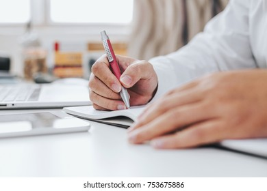 Businessman hand working at a computer and writing on a notepad with a pen in the office.