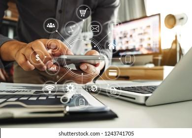 Geschäftsleute, die digitale Marketingmedien in virtuellen Bildschirmen mit Mobiltelefon und modernem Computer mit VR-Icon-Diagramm im Büro in Morgenlicht