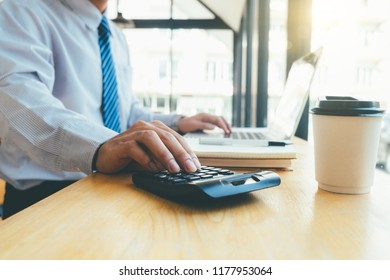 businessman hand working with finances about cost and calculator and laptop with tablet on withe desk at office warm colours sun light