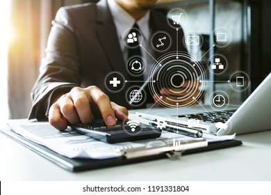 businessman hand working with finances about cost and calculator and laptop with tablet on withe desk at office VR icon in morning light