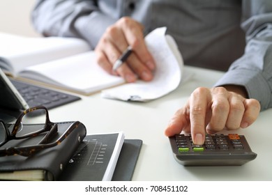 businessman hand working with finances about cost and calculator and laptop with mobile phone on withe desk in modern office