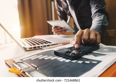 businessman hand working with finances about cost and calculator and laPtop with tablet and smartphone on withe desk in modern office in morning light