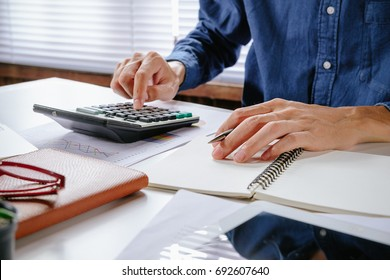 Businessman hand working with financial data and calculator on white desk in modern office.Business analysis and strategy concept.