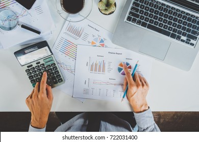 Businessman hand working with financial data and calculator  on wihite desk in modern office.Business analysis and strategy concept.