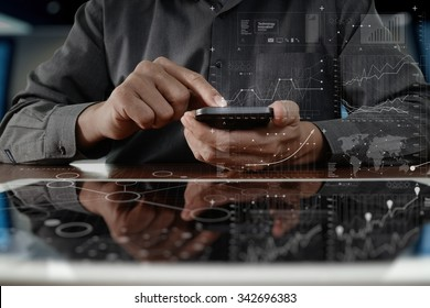 businessman hand working on digital tablet computer and smart phone with graphics layer business strategy and social media diagram on wooden desk