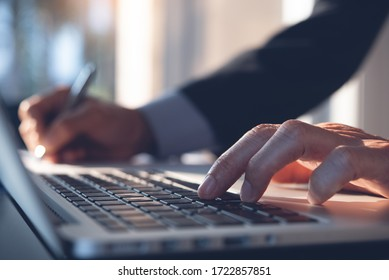 Businessman hand working on laptop computer, typing keyboard, writing on notebook planning his work in modern office, close up. Project manager, corporate man proofing business report on desk.