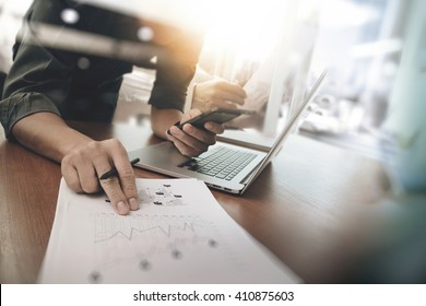 businessman hand working on laptop computer with digital layer business graph information diagram on wooden desk as concept