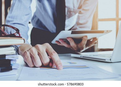 Businessman hand working on laptop computer and holding tablet with digital layer graph information diagram on modern white desk table.Business concept.