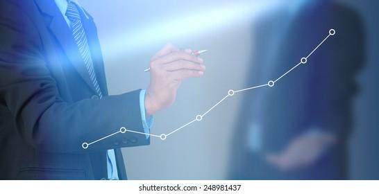 A businessman hand writing a business graph
