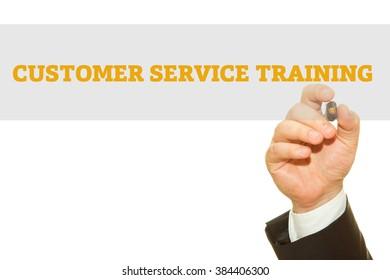 Businessman hand writing Customer Service Training isolated on white.