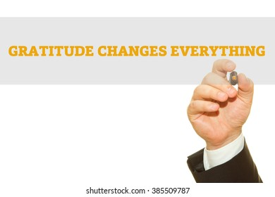 Businessman hand writing Gratitude Changes Everything isolated on white.