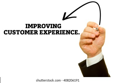 Businessman hand writing IMPROVING CUSTOMER EXPERIENCE message on a transparent wipe board.