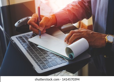 Businessman hand writing and signing white empty bank checkbook with modern computer notebook and wireless mouse on the desk at office. Payment by check,paycheck,payroll ,cheque sign conceptual.