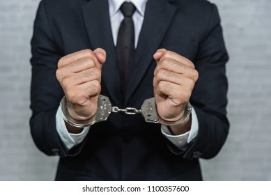 businessman in handcuffs arrested isolated on gray background