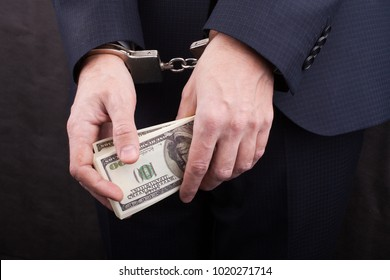 Businessman in handcuffs holding bribe, closeup