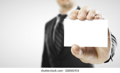 Businessman handing a blank business card over white background