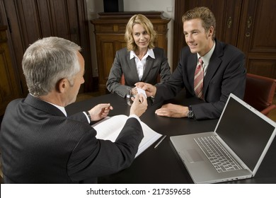Businessman handing couple his business card