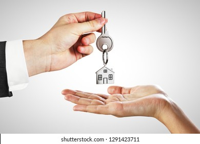 Businessman handing key on white background. Mortgage and agent concept