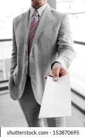 Businessman handing a mailing envelope as a business concept